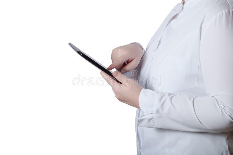 En kvinna i en vit enhetlig ämbetsdräkt med den elektroniska apparaten i hennes mummel arkivbild
