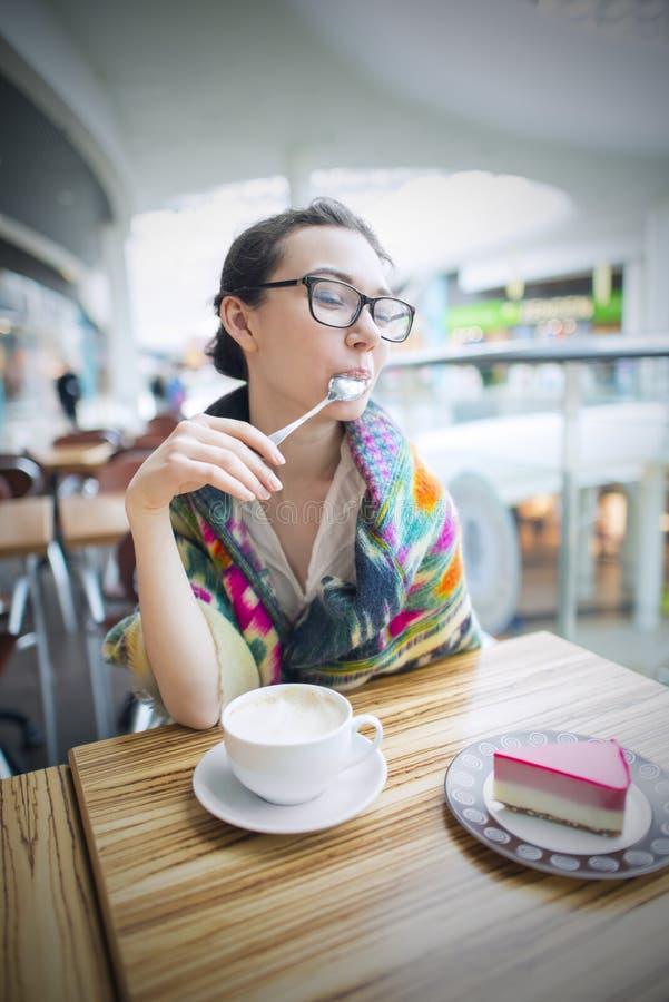 En kvinna i ett kafé dricker kaffe arkivbild