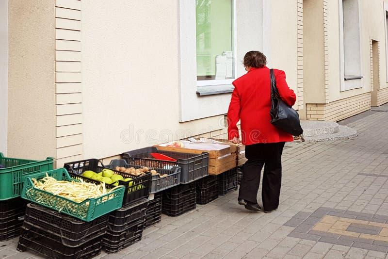 En kvinna i ett rött lag väljer grönsaker som läggas ut i askar på ingången till en livsmedelsbutik på gatan Skördfält och eller royaltyfria foton