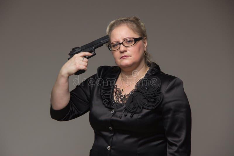 En kvinna i ett svart omslag med en svart pistol arkivfoto