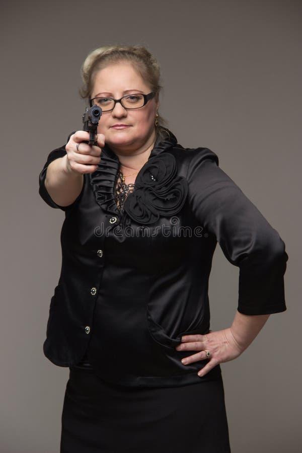 En kvinna i ett svart omslag med en svart pistol arkivbilder