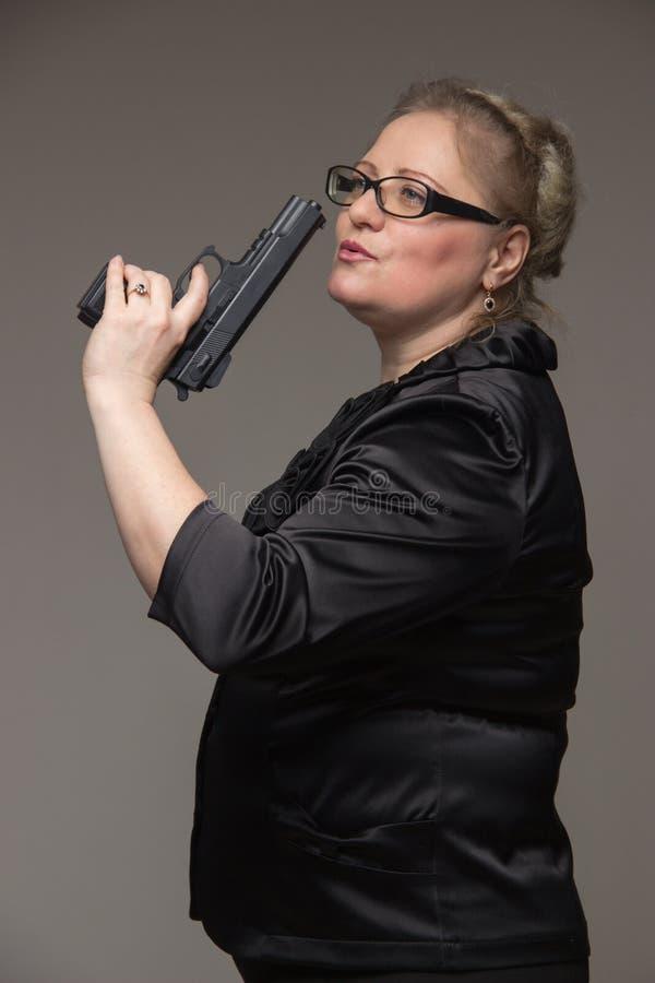 En kvinna i ett svart omslag med en svart pistol royaltyfri foto