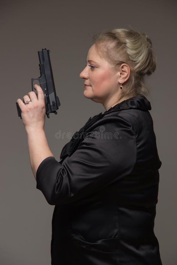 En kvinna i ett svart omslag med en svart pistol fotografering för bildbyråer