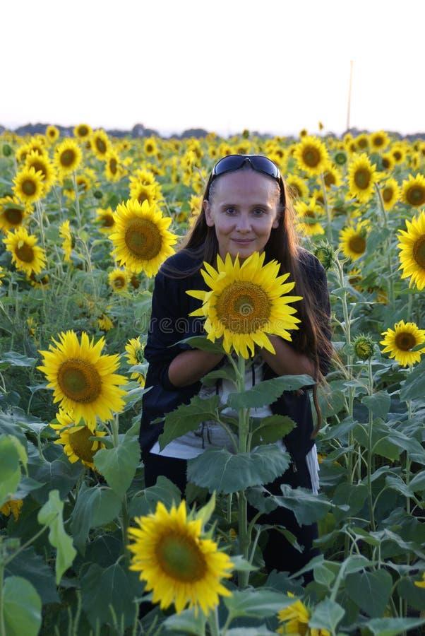 En kvinna i fältet av solrosor i sommartid royaltyfria bilder