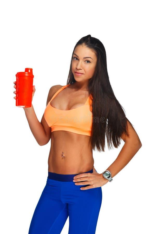 En kvinna i färgrik sportswearinnehavflaska av vatten arkivfoton