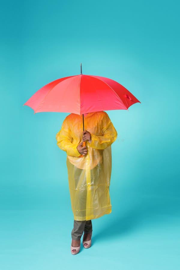 En kvinna i en gul regnrock dolde under ett rött paraply Det står på en blå bakgrund, framsidan är inte synligt arkivfoton