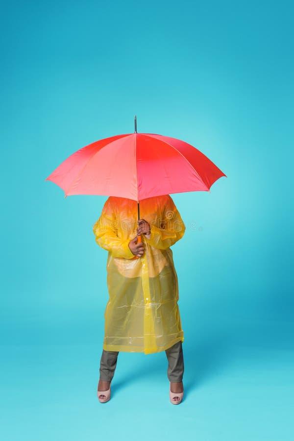 En kvinna i en gul regnrock dolde under ett r?tt paraply Det st?r p? en bl? bakgrund, framsidan ?r inte synligt royaltyfri fotografi