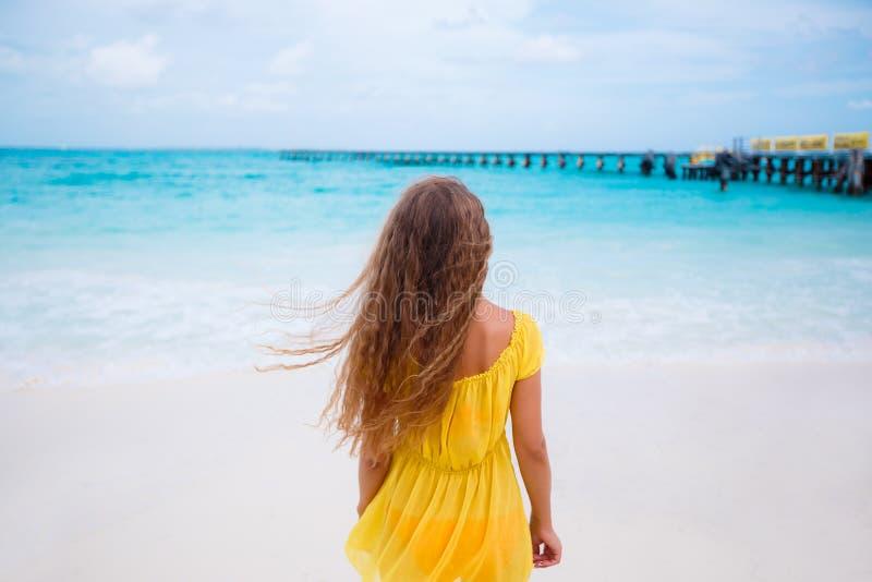 En kvinna i gula sundress på en tropisk strand royaltyfri fotografi