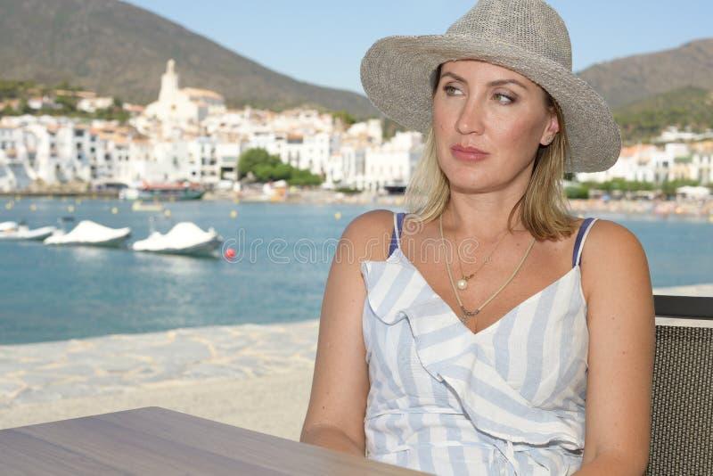 En kvinna i en hatt som sitter på en terrass på promenaden av en välkänd medelhavs- stad, kallade Cadaqués med byn i arkivbild