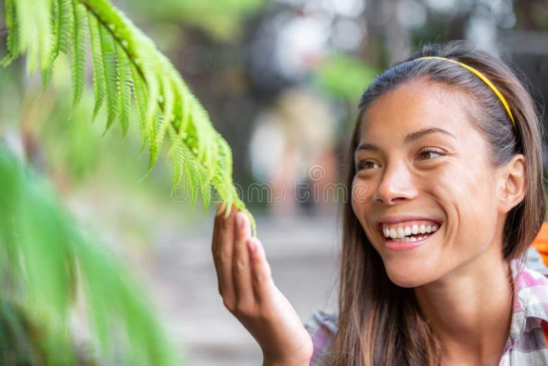 En kvinna i naturparken som rör växter för miljöklass om vildmark i naturundervisning i skogstasiatiska royaltyfri fotografi
