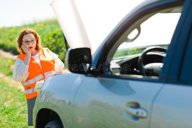 En kvinna i ?ppen bilh?tta f?r orange v?st av den brutna bilen arkivbild