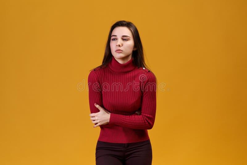 En kvinna i en röd halvpolokrage rymmer hennes mage Flickan har en mageknip Från strängt smärta den härliga unga kvinnan önskar a royaltyfri foto