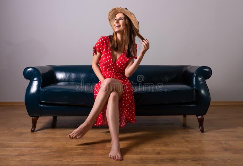 En kvinna i en r?d kl?nning som sitter p? en soffa arkivfoto