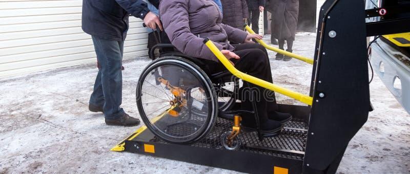 En kvinna i en rullstol på en elevator av ett specialiserat medel för folk med handikapp Taxi för handikappade personer Gul stång arkivbilder