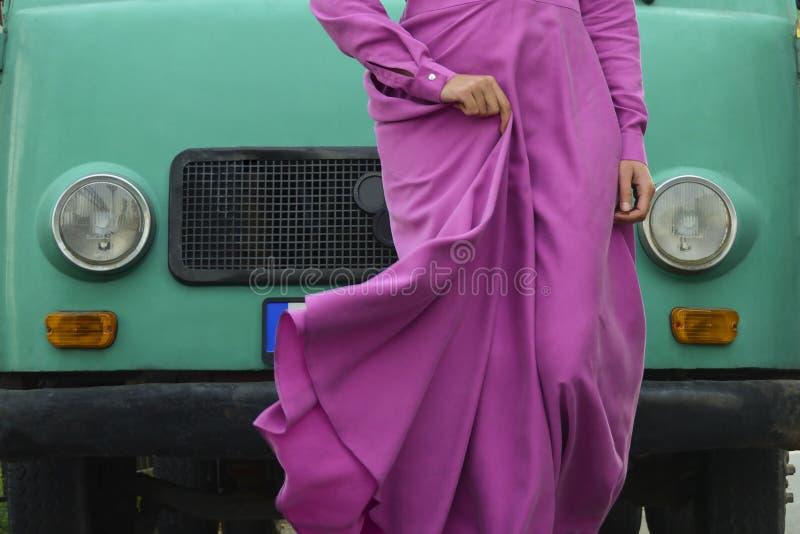 En kvinna i en siden- klänning för magentafärgad fuchsia framme av en mintkaramellskåpbil på gatan arkivbild