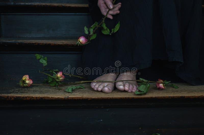 En kvinna i en svart klänning som rymmer en bukett av döda rosor royaltyfri foto