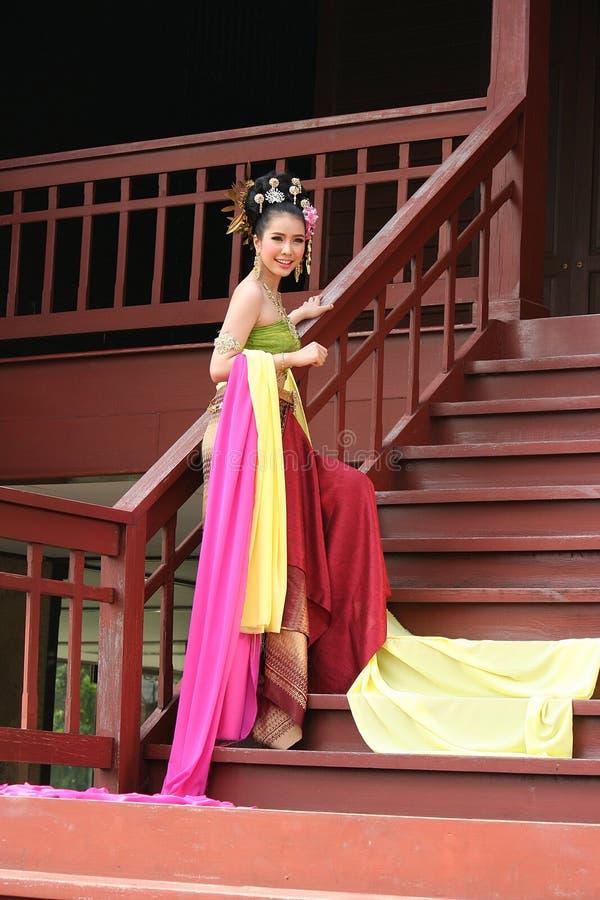 En kvinna i THAILÄNDSK RETRO KLÄNNING poserar för ett fotografi royaltyfri foto