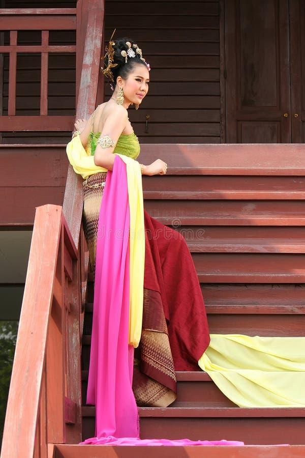 En kvinna i THAILÄNDSK RETRO KLÄNNING poserar för ett fotografi royaltyfria foton