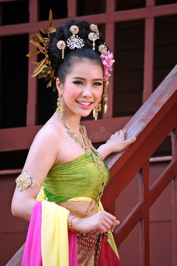 En kvinna i THAILÄNDSK RETRO KLÄNNING poserar för ett fotografi royaltyfri fotografi