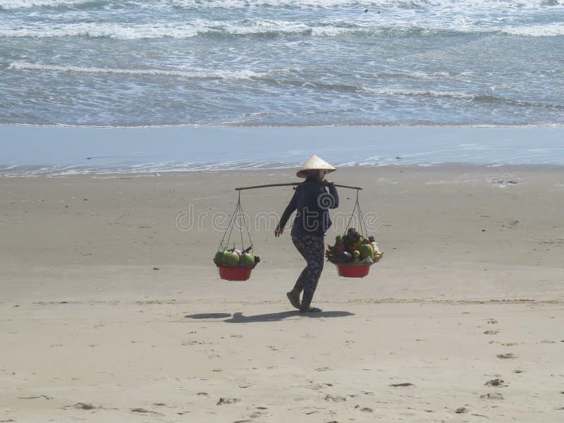 En kvinna i en vietnamesisk hatt promenerar en sandig strand med två korgar av frukt arkivbilder