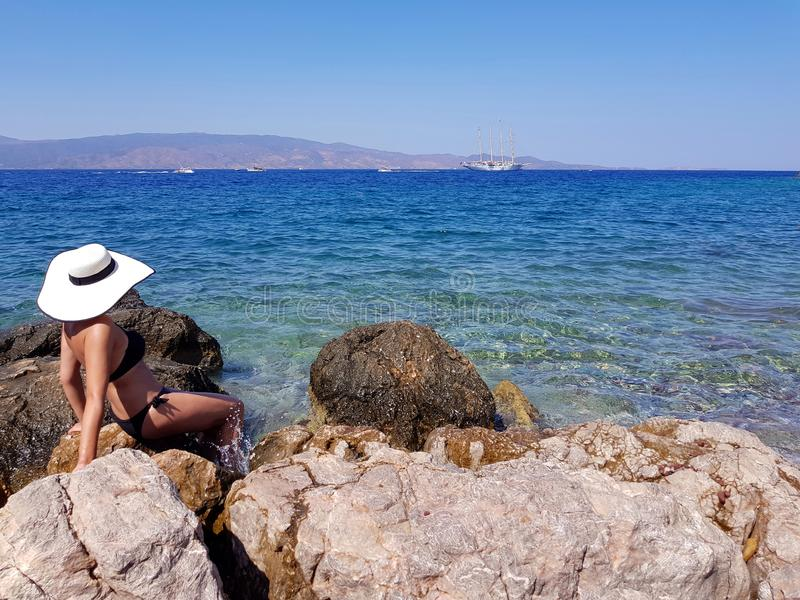 En kvinna i vitt hattsammanträde på den stenigt kusten och se för hav arkivfoto