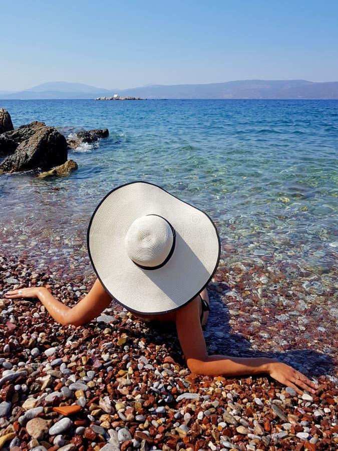 En kvinna i vitt hattsammanträde på den stenigt kusten och se för hav royaltyfria foton