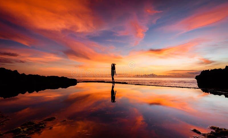 En kvinna i en yoga poserar silhouetted mot en solnedgång med hennes reflexion i vattnet 2 royaltyfri foto