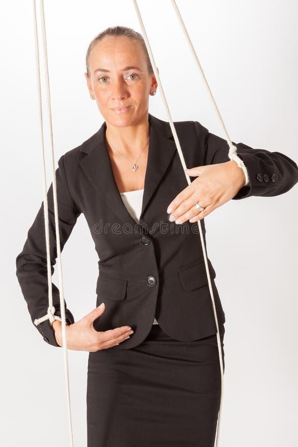 En kvinna inställs på en repnågot liknande en marionette royaltyfri bild