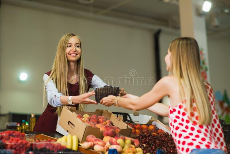 En kvinna köper bär i marknaden royaltyfria foton