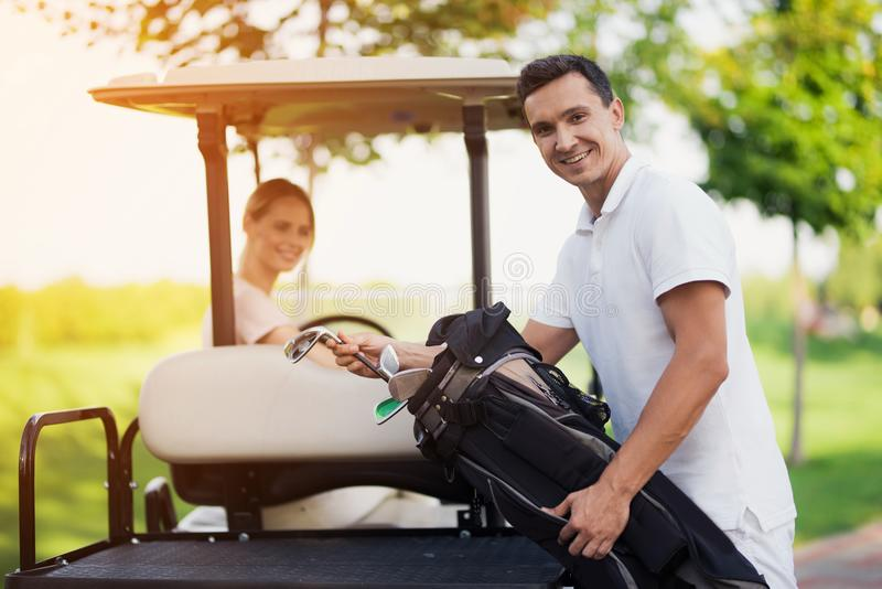 En kvinna kör en golfbil En man i förgrunden står bredvid stammen och drar ut en golfklubb arkivfoto
