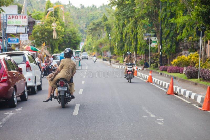 En kvinna kör på en moped i Bali/Indonesien royaltyfri foto