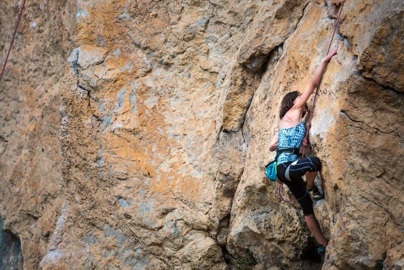 En kvinna klättrar vagga arkivfoton