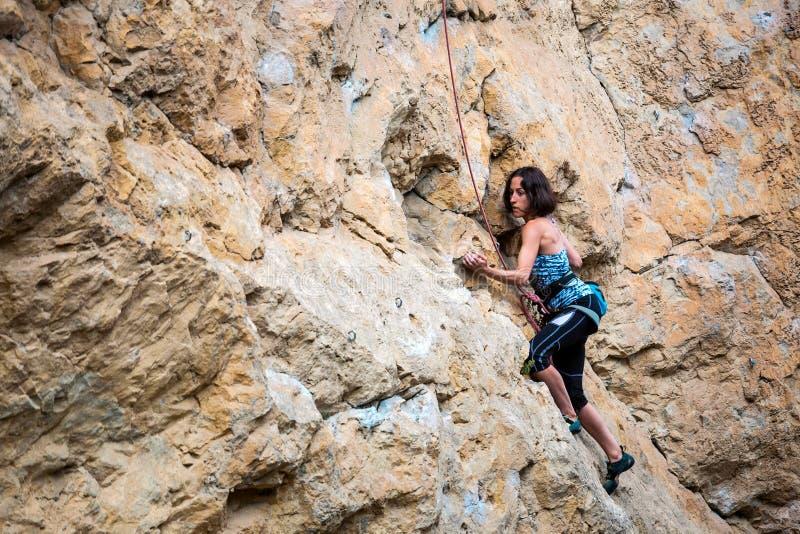 En kvinna klättrar vagga arkivfoto