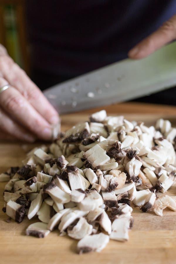 En kvinna klipper champinjoner med en kniv på en träskärbräda royaltyfri foto