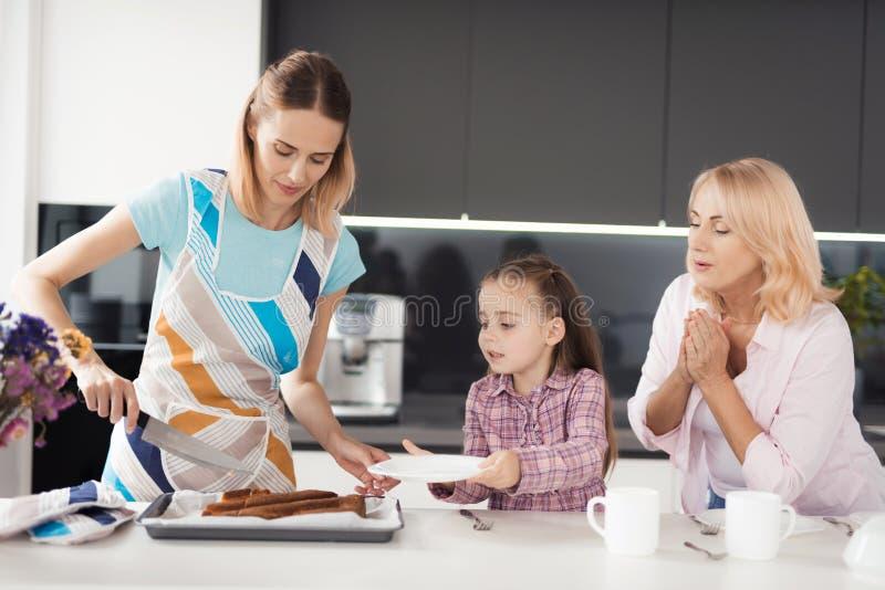 En kvinna klipper en hemlagad kaka för hennes moder och dotter, som hon bakade precis arkivbild
