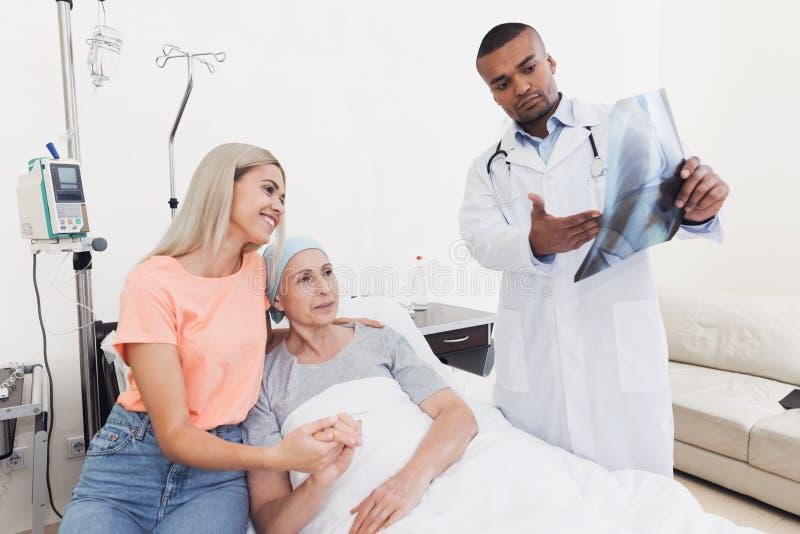 En kvinna kom att se hennes moder, som hade cancer Doktorn rymmer hennes röntgenstråle arkivbild