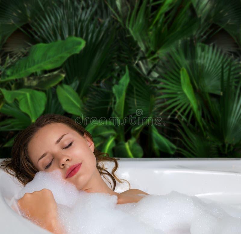 En kvinna kopplar av i varmt bad badar med tvålskum royaltyfri bild