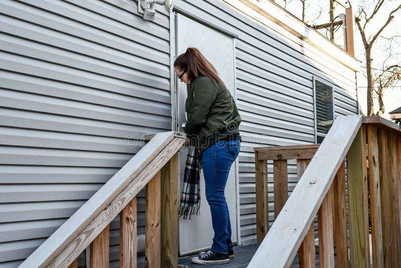 En kvinna låser hennes ytterdörr, som hon lämnar hem royaltyfri bild