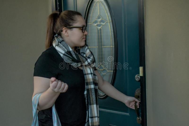 En kvinna låser hennes ytterdörr, som hon lämnar hem med en sjösäck över en arm royaltyfria bilder