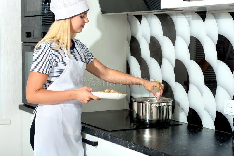 En kvinna lagar mat spagetti och korvar arkivfoton
