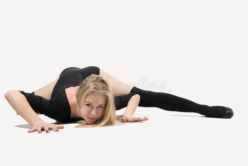 En kvinna med en goda som sträcker på golvet arkivfoto