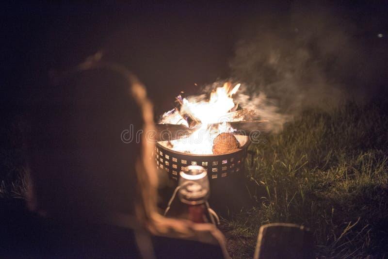 En kvinna med långt hår tycker om vin och en varm utvändig brand fotografering för bildbyråer