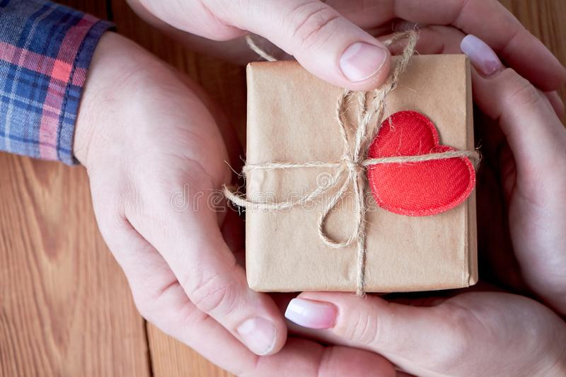 En kvinna med en man som rymmer en gåva i hans hand på en träbakgrund på valentin dag eller på jul royaltyfria foton