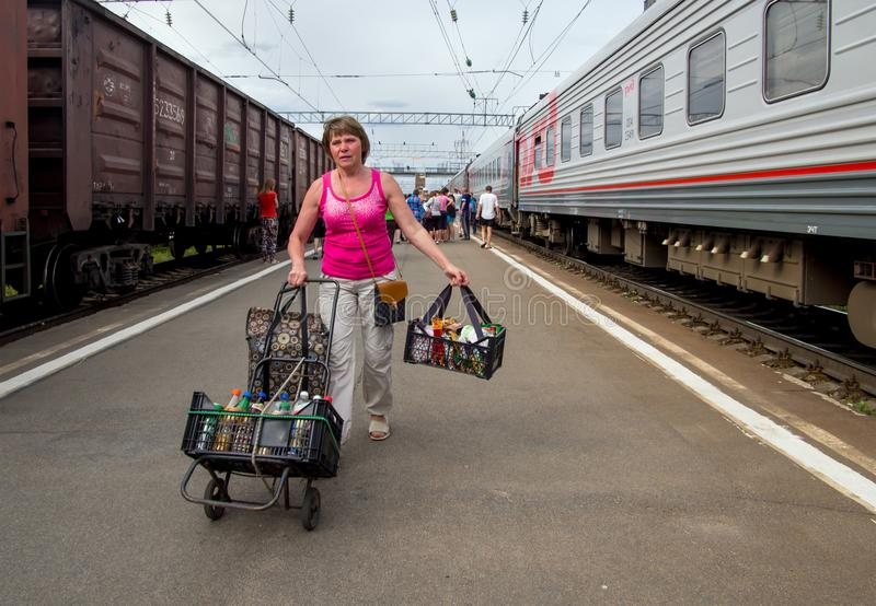 En kvinna med mat går på plattformen av järnvägsstationen Petrozavodsk arkivfoto