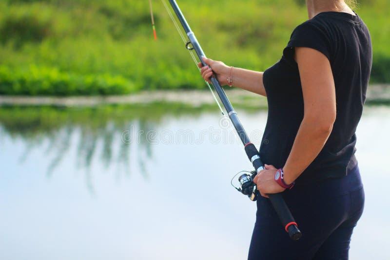 En kvinna med metspölås fiskar i sjön arkivfoton