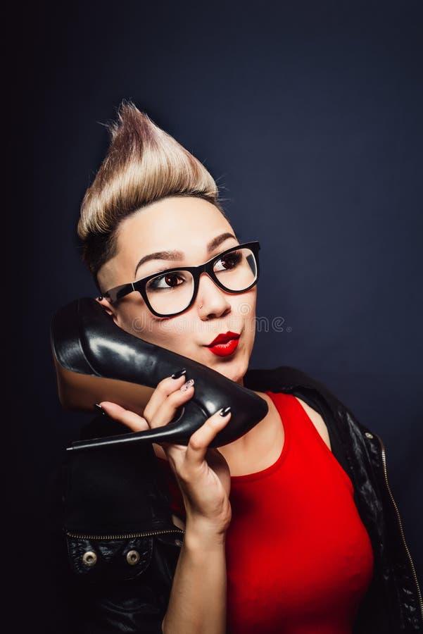 En kvinna med en mohawk och bärande exponeringsglas säger fotografering för bildbyråer
