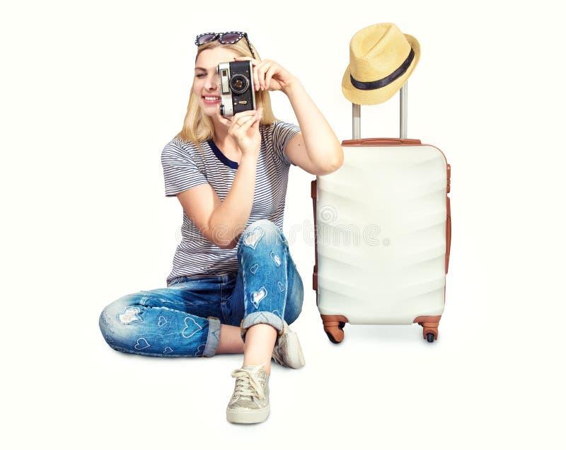 En kvinna med en resväska och en kamera går på ett lopp royaltyfria bilder