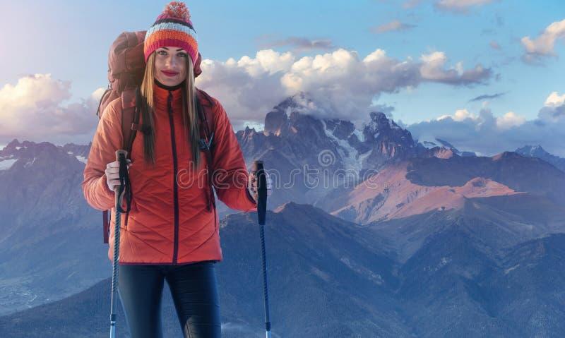 En kvinna med en ryggsäck vilar överst av berget och tycker om sikterna av dalen arkivbilder