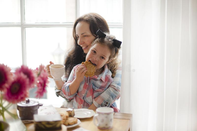 En kvinna och lite dottern äter frukosten hemma på en tabell vid fönstret Lycklig bra morgon för familj och för frukost på royaltyfri foto