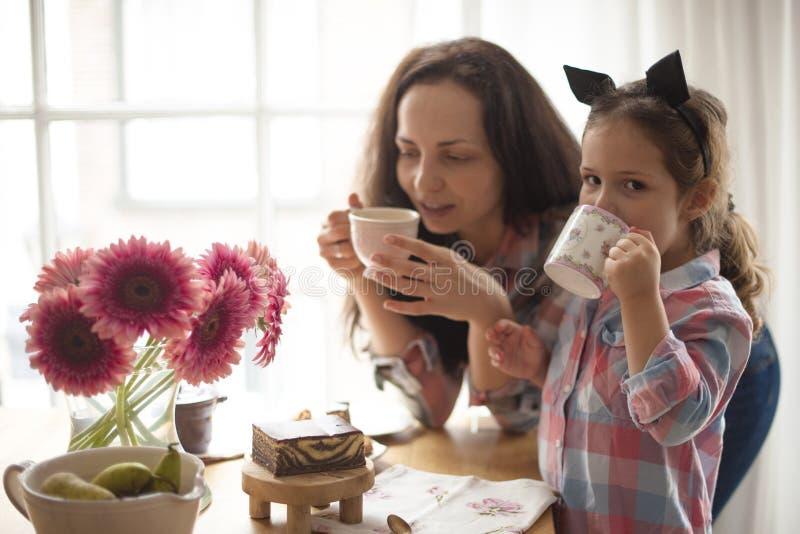 En kvinna och lite dottern äter frukosten hemma på en tabell vid fönstret Lycklig bra morgon för familj och för frukost på arkivfoto